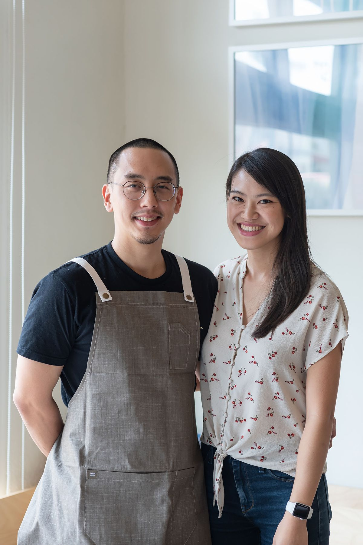 A portrait of the restaurant's owners standing side by side and smiling. Chris Yang, on the left, wears an apron. Maggie Ho, on the right, has long dark hair and wears a white and red shirt.
