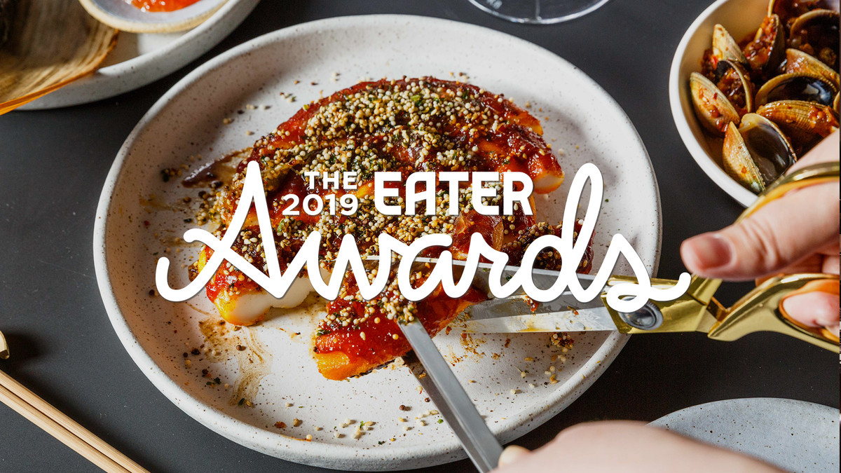 Hands cut into a rice cake, with the 2019 Eater awards logo on top of it.