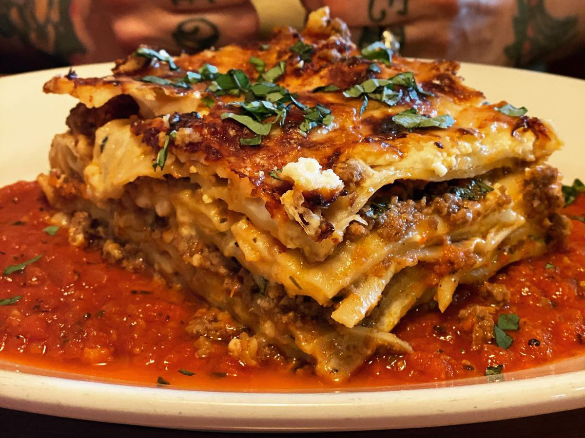 A slice of cheesy lasagna on a plate in front of a person holding a knife and fork