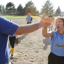 Brad Thomas, left, who has been coaching his daughter's accelerated softball team for the past five years, high fives Kamryn Henriod during a scrimmage at Dewey Bluth Park in Sandy, Utah, Thursday, June 9, 2016.