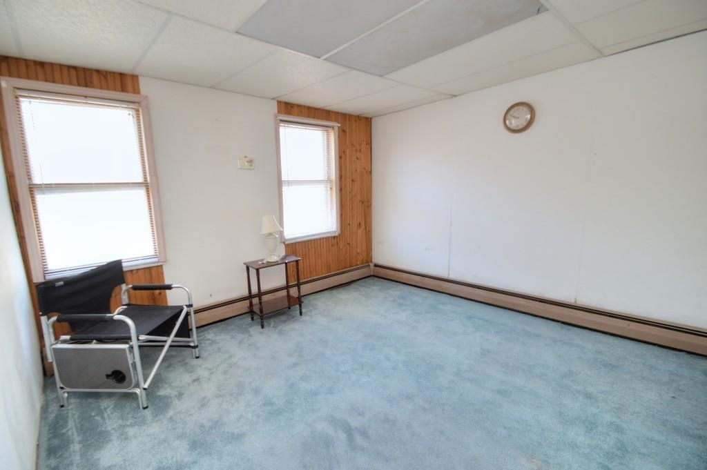 A small, largely empty bedroom with two windows.