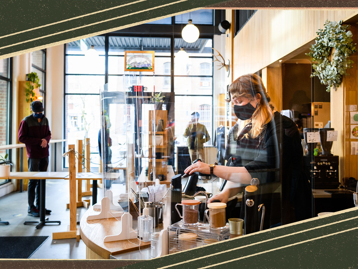 A woman wearing a mask makes coffee behind a barista counter in the Pearl District.