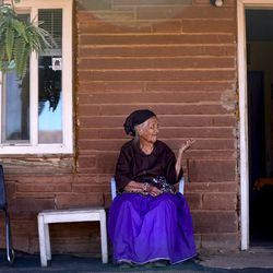 Ruth Holiday, 84, sits outside of her home in Oljato-Monument Valley, San Juan County, as Utah Navajo COVID-19 Reliefprogramemployees and Utah Navajo Health System volunteers deliver food to her and her husband on Thursday, April 30, 2020. A sign hangs on the door of her home notifying visitors not to enter because her husband has a respiratory illness. TheNavajo Nation has one of the highest per capita COVID-19 infection rates in the country.