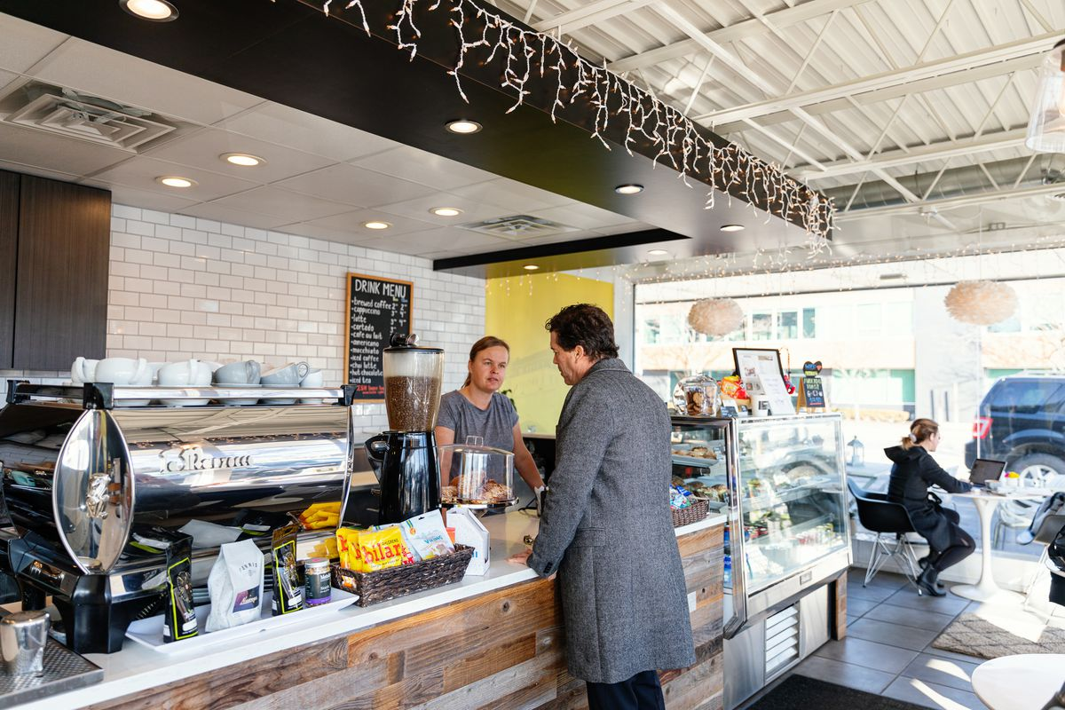 Ingela stands beside an espresso machine at the counter and helps a man in a long gray coat.
