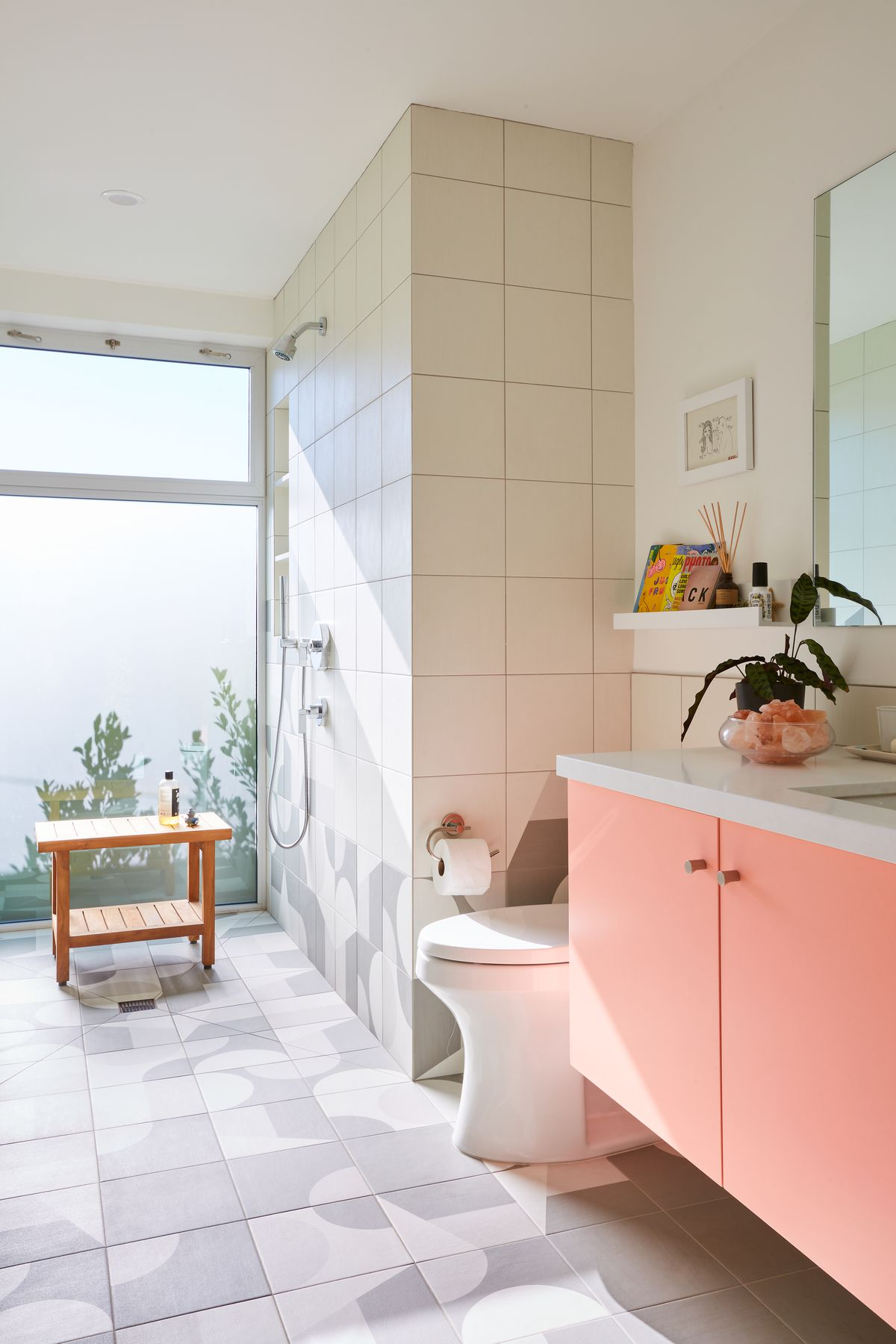 A bathroom with pink cabinetry and gray and white patterned floor tiles.