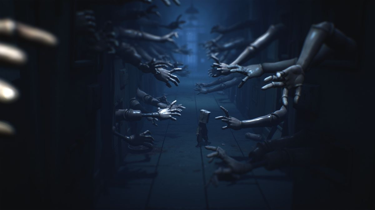 A character walks through a hallway, as dozens of doll arms reach out in a screenshot from Little Nightmares 2