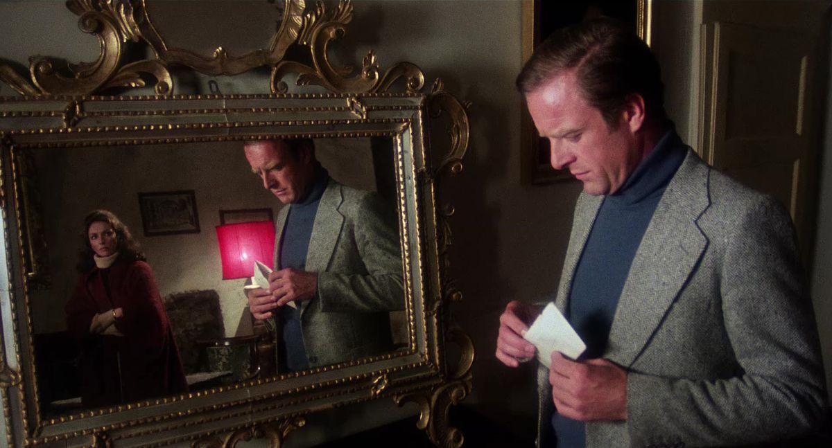 Franscesco Ducci (Gianni Garko) and Virginia Ducci (Jennifer O'Neill) opening a letter opposite of a reflecting mirror.