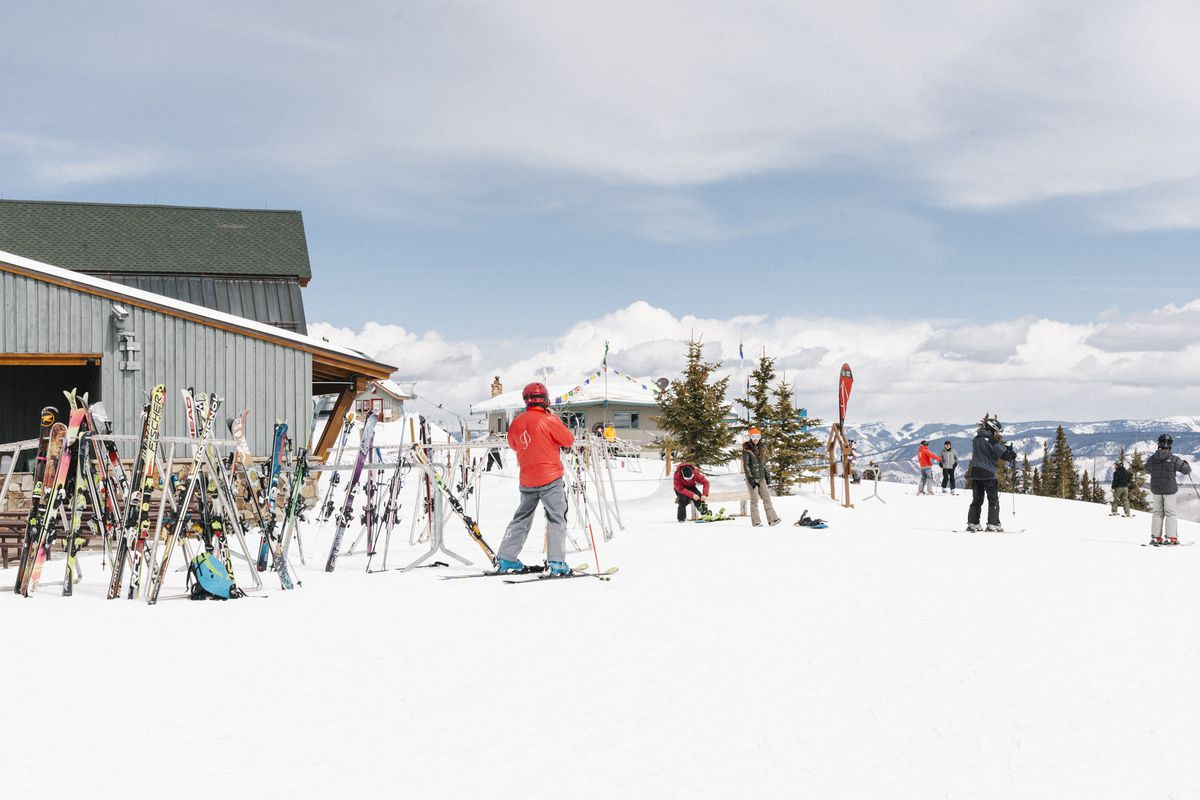 Skiers and skis in bright colors at the top of a mountain.