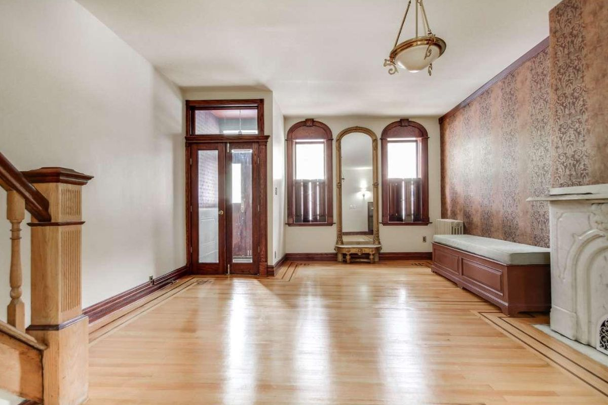 A living room with hardwood floors, a marble fireplace, and foyer.