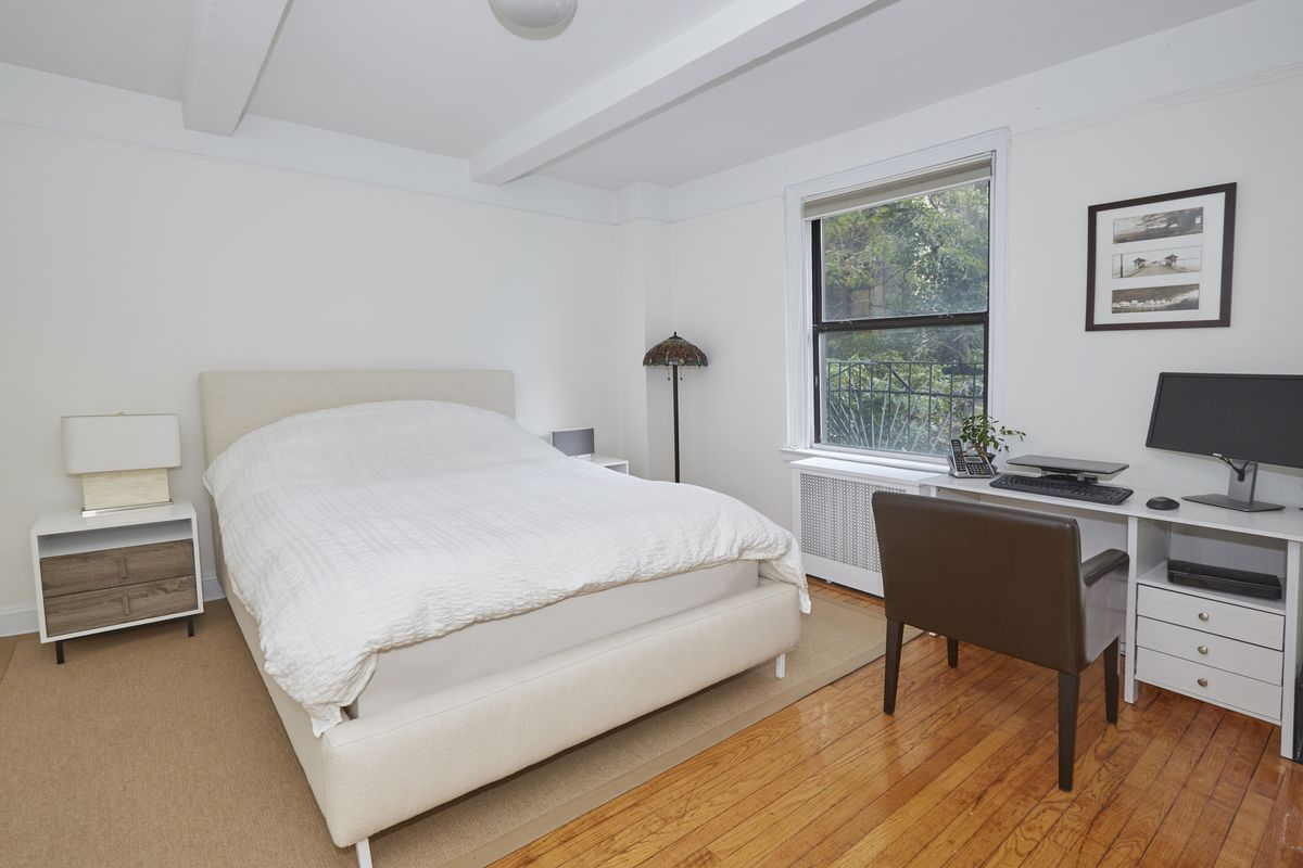 A bedroom with a small bed, a window, beamed ceilings, and hardwood floors.