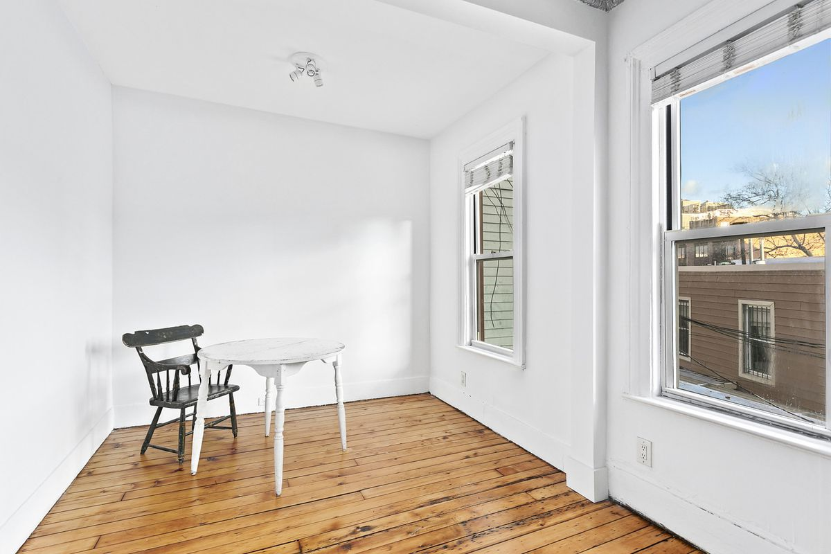 A room with hardwood floors, two windows, white walls, and a white table with a chair.