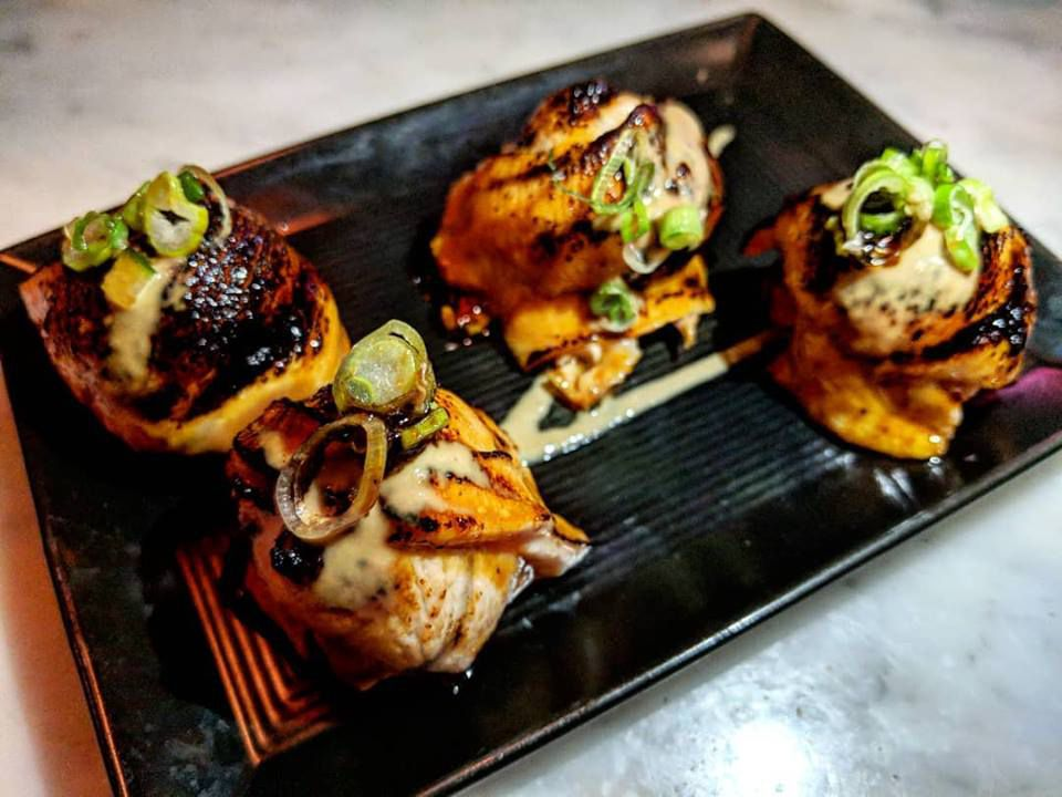 four pieces of torched salmon belly garnished with scallions sit on a black plate
