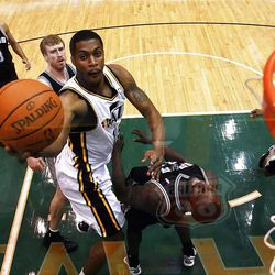 Utah Jazz forward Derrick Favors (15) tries to lay the ball up over San Antonio Spurs forward DeJuan Blair (45) as the Utah Jazz and the San Antonio Spurs play Monday, Feb. 20, 2012 at Energy Solutions arena in Salt Lake City. Spurs won 106-102