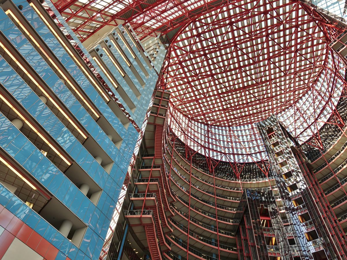 The soaring atrium of the Thompson Center is clad with blue and red accents and topped by a large circular skylight.