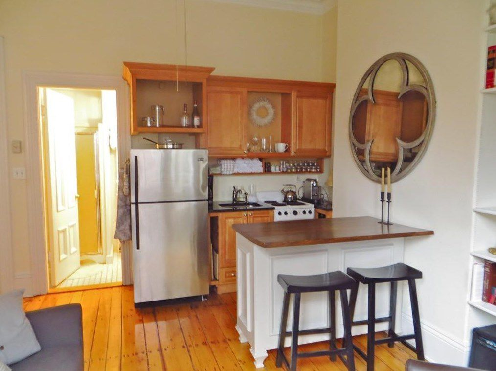 A small open kitchen with a counter jutting out and two stools in front of it.