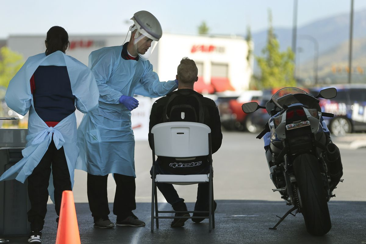 University of Utah Health medical assistant Scott Anderson wears a FlexiFreeze cooling vest as he tests a motorcycle rider for COVID-19 in Farmington on Friday, July 31, 2020. U of U Health is using cooling methods at its testing stations to keep employees comfortable during the extreme heat.