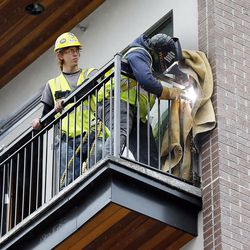 Workers weld a balcony railing in Salt Lake City on Thursday, Feb. 2, 2017, during construction of the 9th East Lofts at Bennion Plaza. The building will provide 68 affordable apartments.