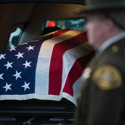 Unified police officer Doug Barney's flag-draped casket waits in the hearse prior to funeral services at the Maverik Center in West Valley City on Monday, Jan. 25, 2016.