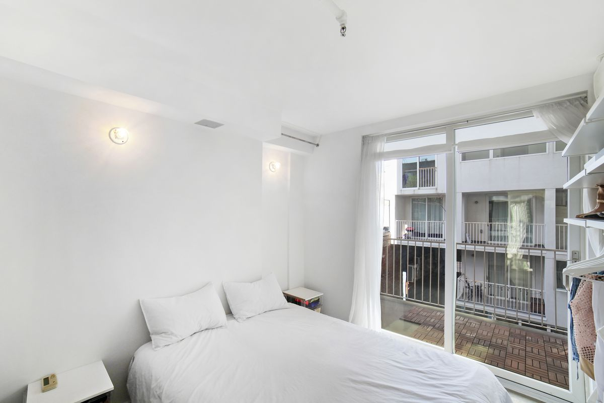 A bedroom with a medium-sized bed, a door that leads to a balcony, and white walls.