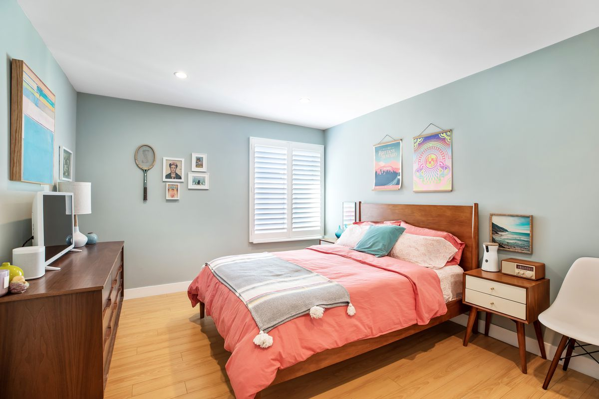 A bedroom with recessed lighting, one window, and a large bed in the center.