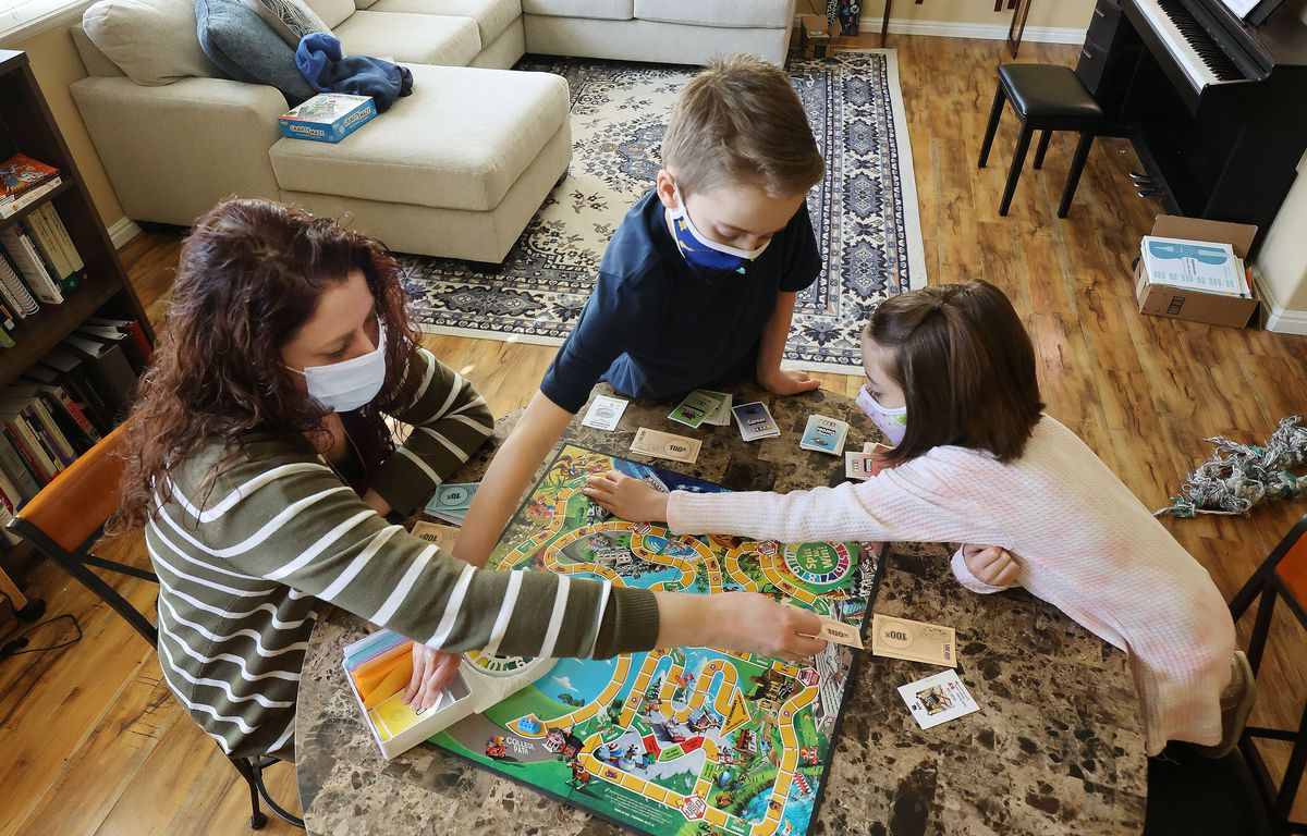 Lisa Sledge, a lawyer and a single mother of two, left, plays a board game with her children Emmett and Bethany at home in West Jordan on Sunday, Feb. 7, 2021. Sledge earned a law degree while raising her children on her own and wants to help others through her new nonprofit Freedom for Resilient Women.
