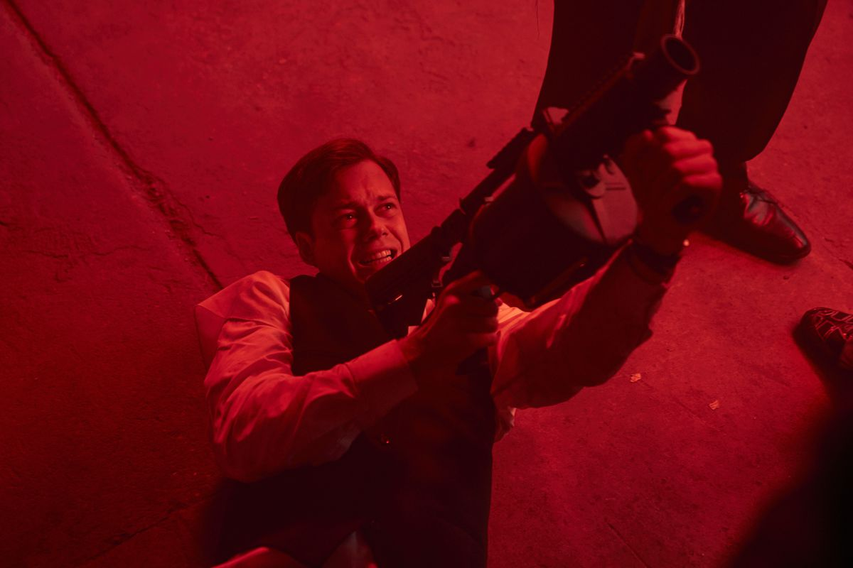 A man on his back in a red-lit space, grimacing and pointing a huge projectile weapon up toward the sky in Naked Singularity
