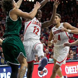 Arizona's Justin Coleman (12) tosses a lob to an open teammate during the Arizona-Utah Valley game in McKale Center on December 6 in Tucson, Ariz.