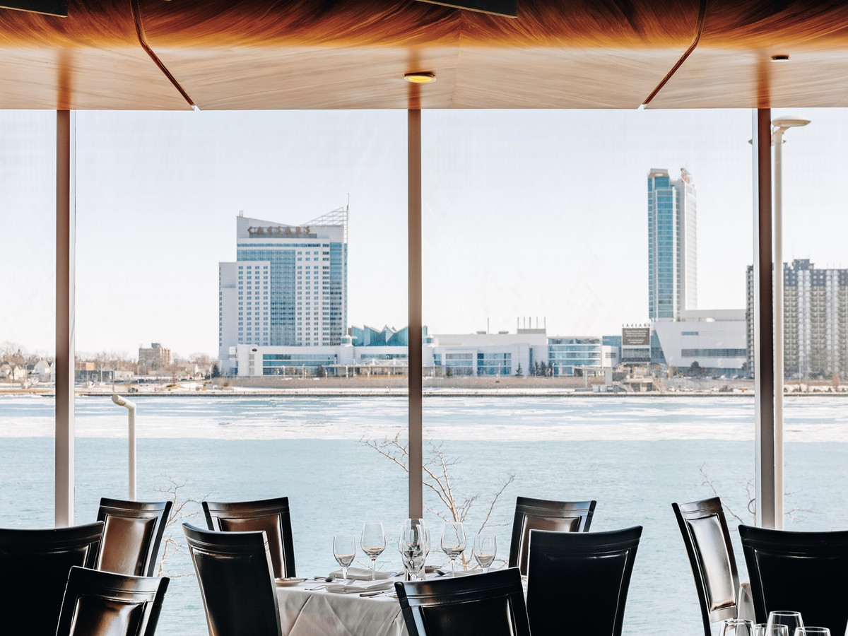 A dining room set on the water, with view of Canada's casino across the river