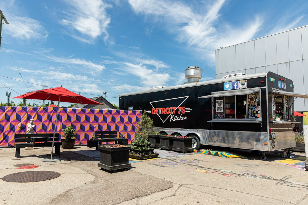 A red umbrella and planters surround several long seats next to the Detroit 75 Kitchen Trailer.