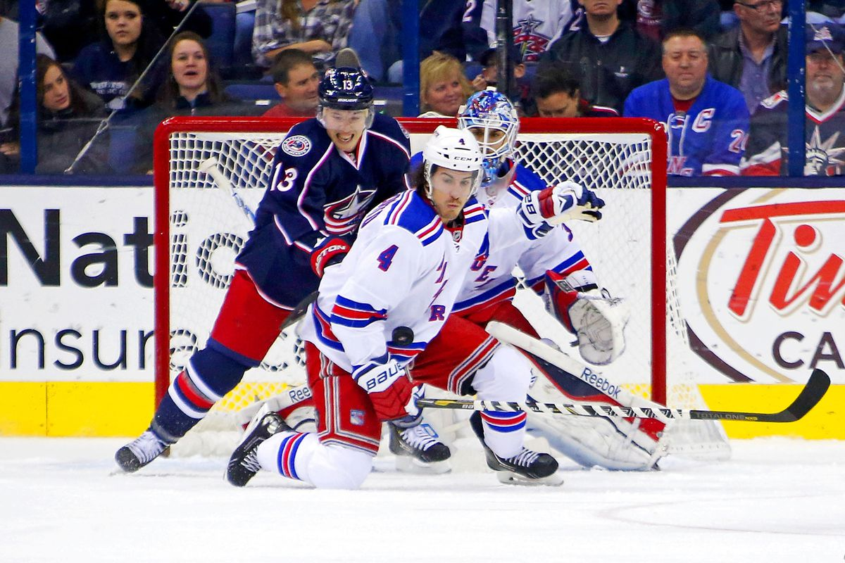 Cam Atkinson checks Michael Del Zotto as he tries to block a shot during an NHL game Thursday between the Blue Jacktets and the Rangers.