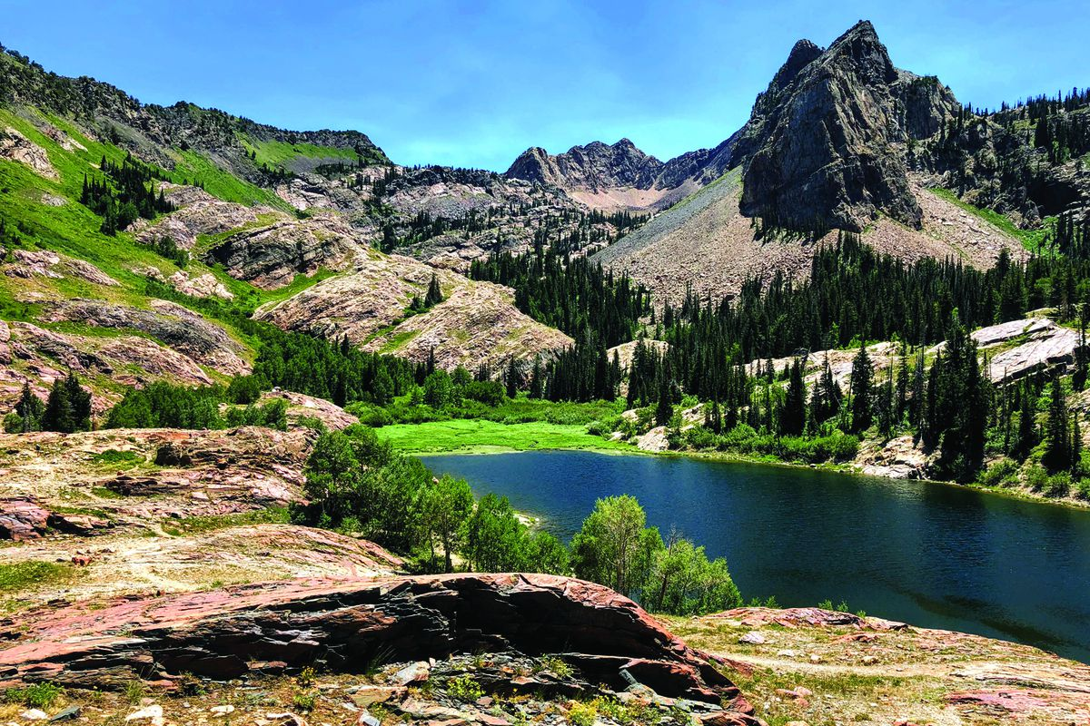 Lake Blanche sits at an elevation of 8,300 feet up Big Cottonwood Canyon at the base of Sundial Peak amid glacier carved deposits.