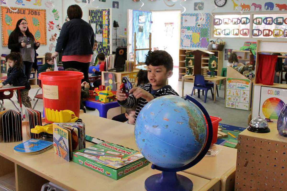 A boy plays in a classroom, just behind a large globe. There are two adults speaking and other kids playing in the classroom.