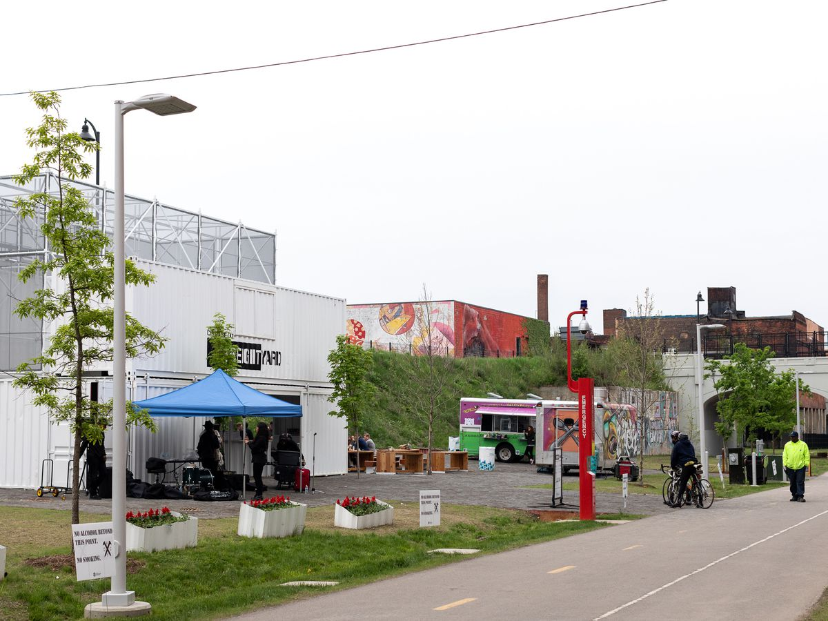 A path alongside a row of buildings that have murals painted on them.
