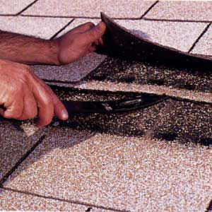 Person using a pry bar to remove damaged roof shingles.