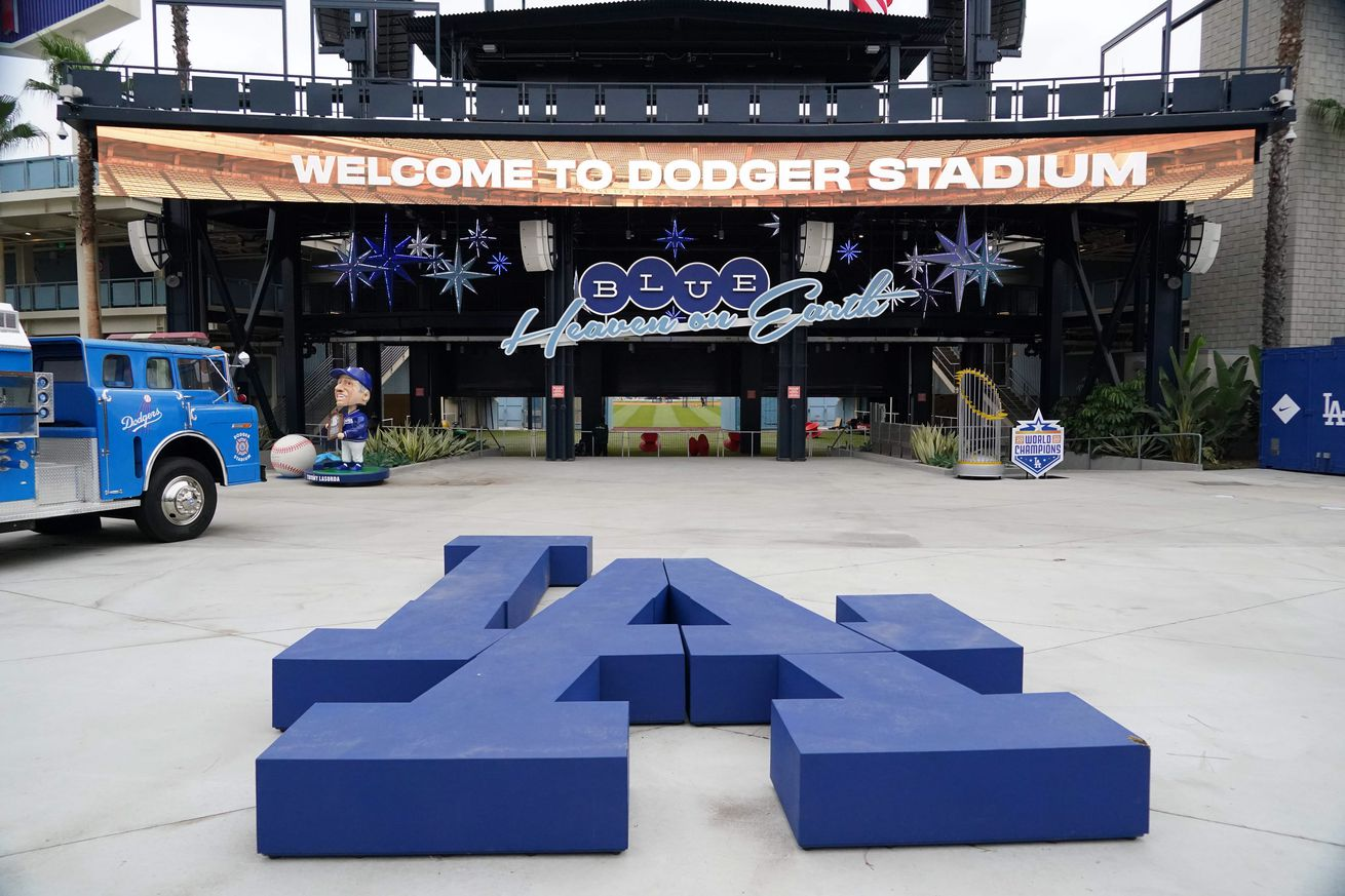 A raised, blue LA logo in front of  a gate leading to Dodger Stadium with a gold and white banner reading Welcome to Dodger Stadium hanging above it