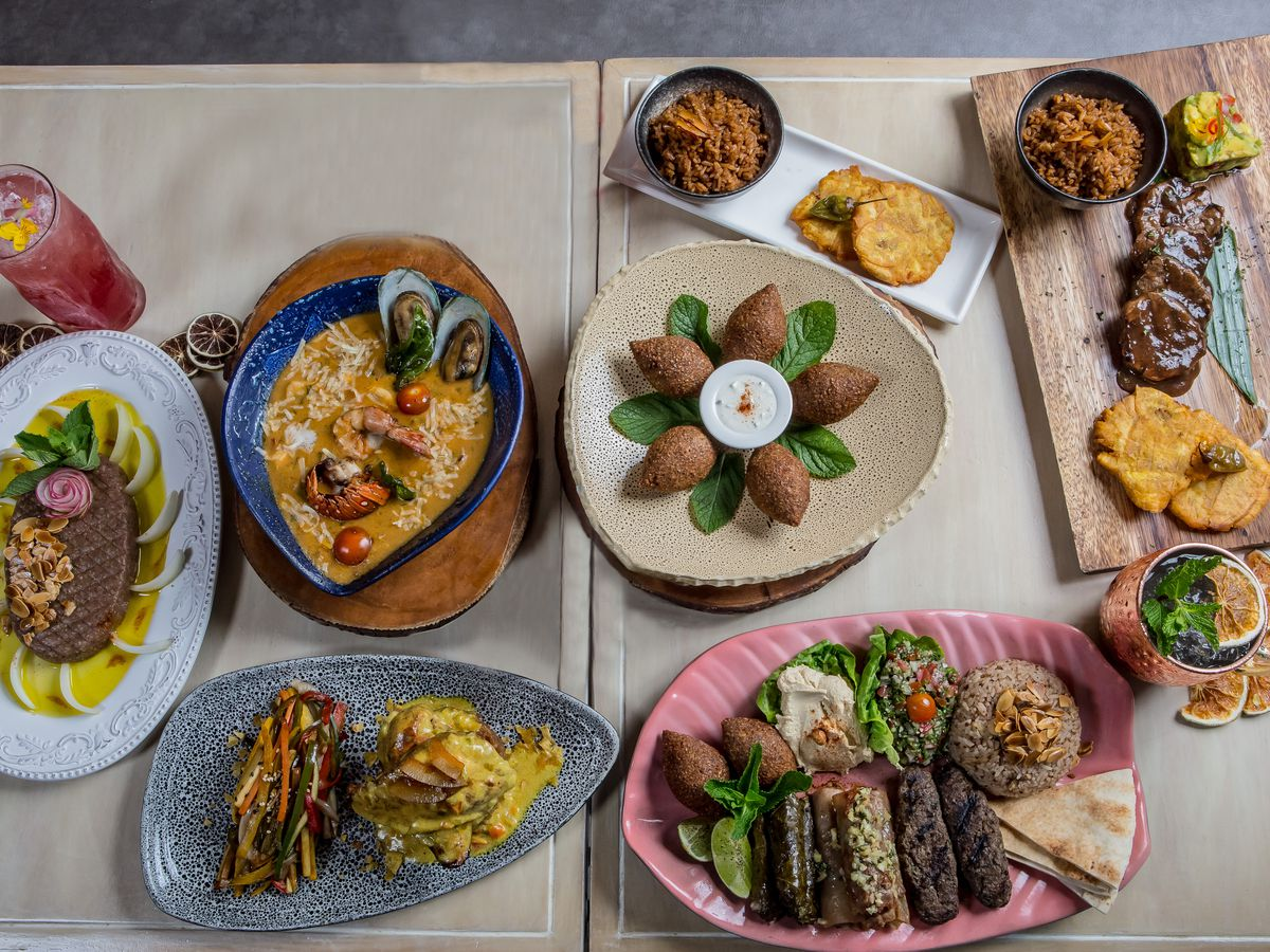 From above, two small wooden tables with neutral coverings topped with a variety of foods in dishes of various shapes, including falafel, stuffed grape leaves, sirloin, fried plantains and dips