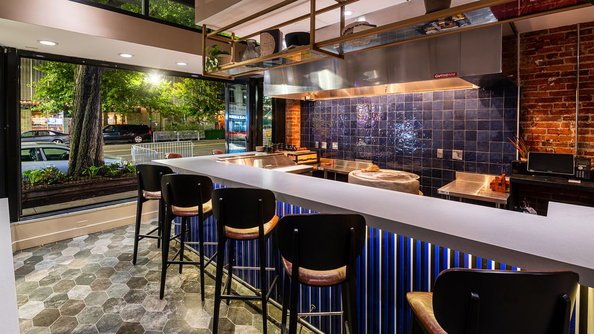 A six-seat tasting bar at the front of Maïz64 contains a gas-fired comal and a backdrop of blue tiles.