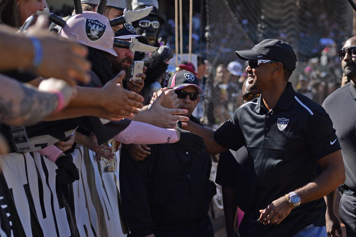 Golfer Tiger Woods shakes hands with members of the Black Hole before the Oakland Raiders vs. San Diego Chargers NFL game at O.co Coliseum in Oakland, Calif., on Sunday, Oct. 12, 2014. (Jose Carlos Fajardo/Bay Area News Group)