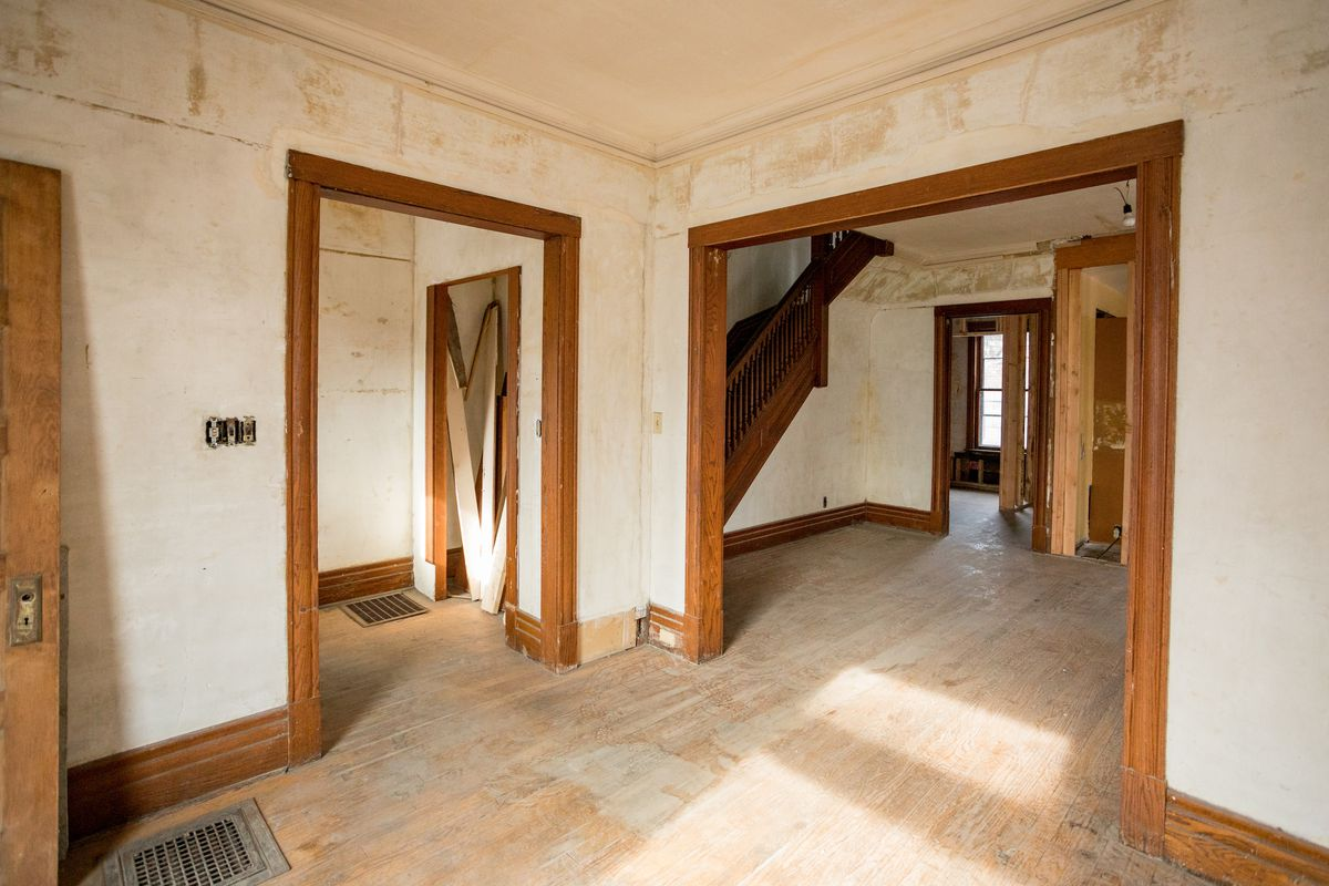 Two entryways with wood trim around the frame. The bigger entryway leads to a large empty room and staircase.