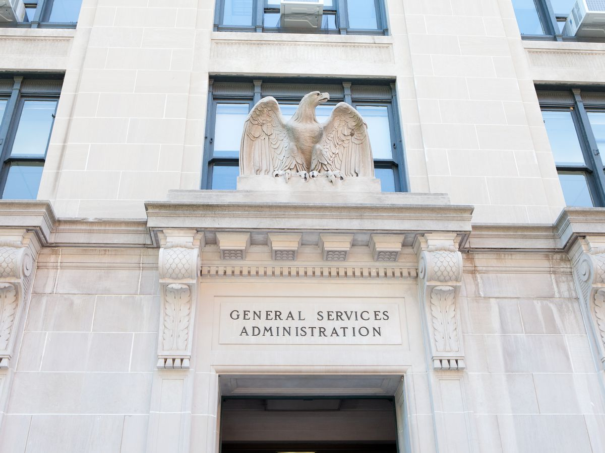The exterior of the United States General Services Administration. The facade is white and there is a statue of an eagle on top of the entryway.