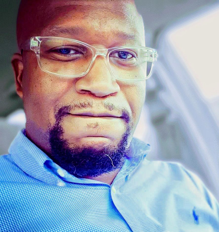 Attractive brown skin man with bald head, glasses, and beard stares at the camera for a headshot.