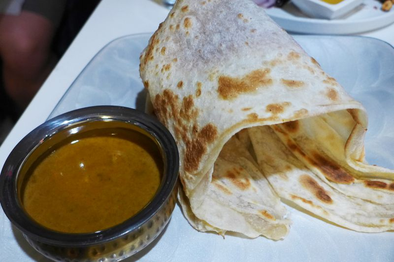 Flatbread with small bowl of peanut sauce.