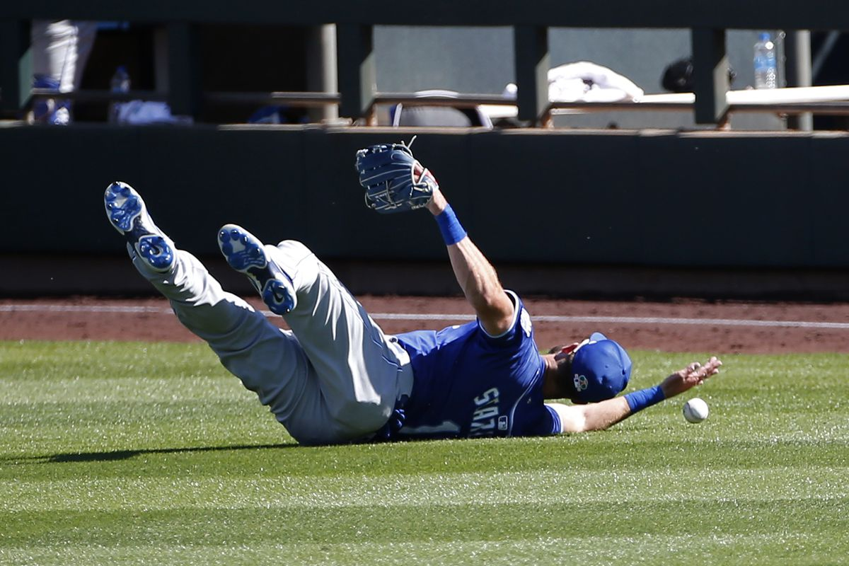 Bubba Starling #11 of the Kansas City Royals reaches for the ball as he as he fails to complete a diving catch on a line drive hit by Asdrubal Cabrera #14 of the Arizona Diamondbacks during the fifth inning of the MLB spring training baseball game at Salt River Fields at Talking Stick on March 20, 2021 in Scottsdale, Arizona.