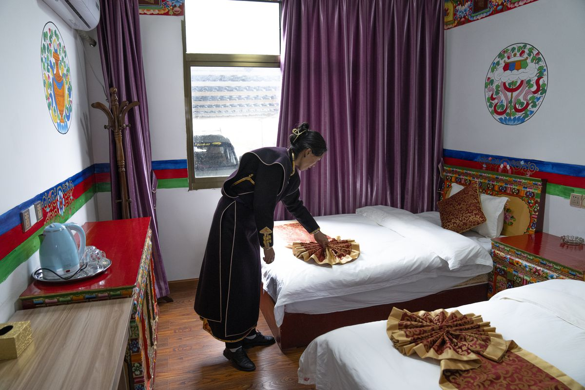 A woman in an ethnic dress adjusts a bedspread at her tourist host family in Zhaxigang village near Nyingchi, west China's Tibet Autonomous Region.