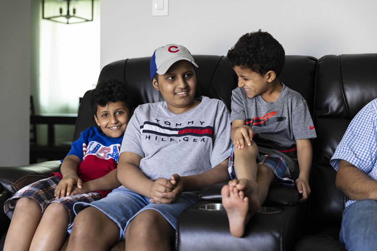 Mohamed, from left, Abdullah, Ali, and Mohsin Omer relax on the couch at their home in Chicago Ridge, Illinois, Tuesday, June 22, 2021.