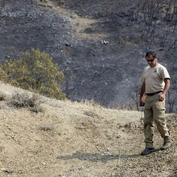 Rudy Sandoval, Incident Commander trainee for Utah's Department of Natural Resources Forestry Division, surveys the charred hillside of Bybee Road in Ogden on Wednesday, Sept. 6, 2017. At least six structures, including multiple homes, have been destroyed after a brush fire erupted in Weber Canyon Tuesday morning.