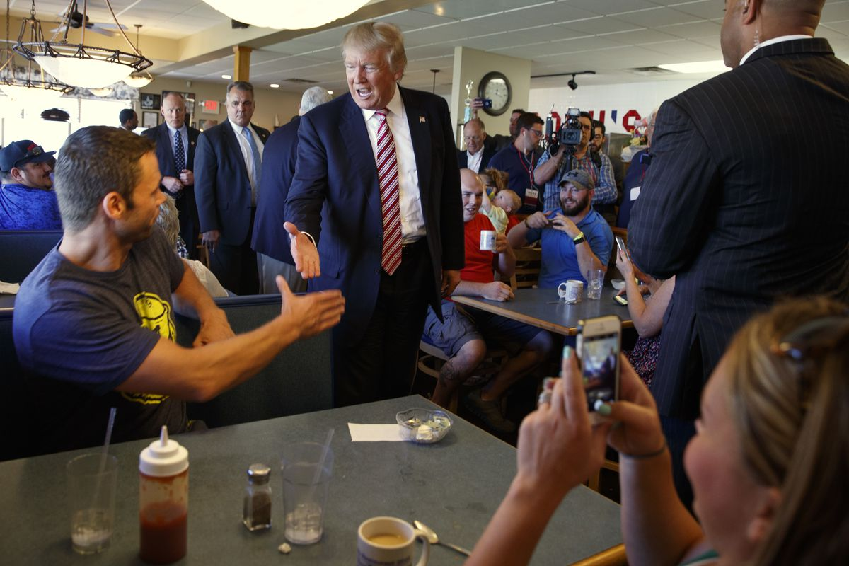 Republican presidential candidate Donald Trump shakes hands during a visit to Goody's Restaurant Monday in Brook Park, Ohio. | AP Photo/Evan Vucci