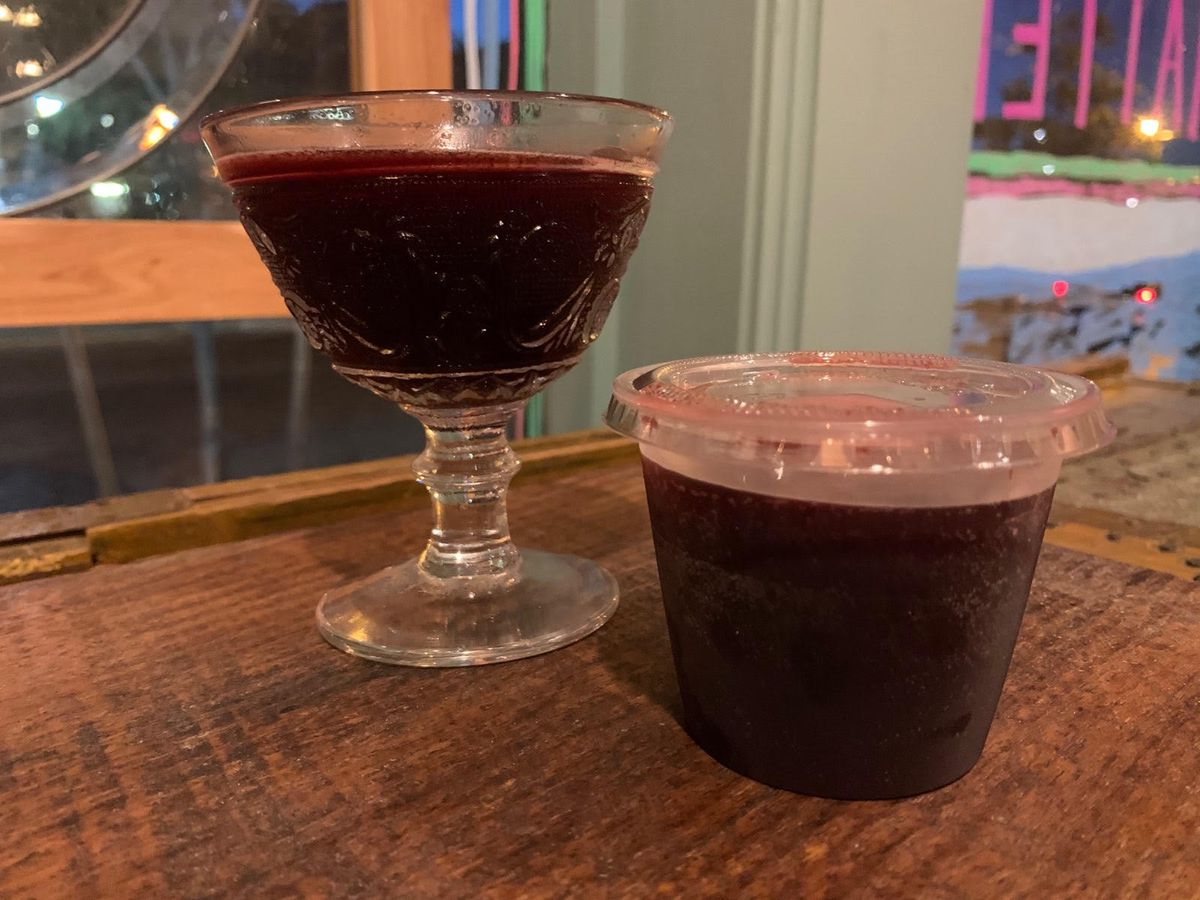 A dark purple drink is shown in fancy glassware and a small plastic to-go cup, both sitting on a wooden counter.