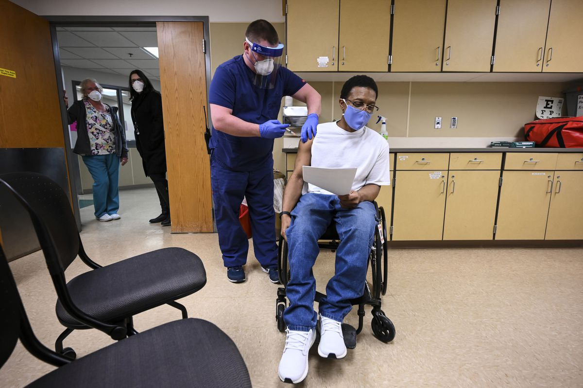 Kelly Markham, a registered nurse supervisor at Minnesota's Faribault Prison, administers the state's first COVID-19 vaccination to a medically vulnerable inmate, Edward Anderson, in January.