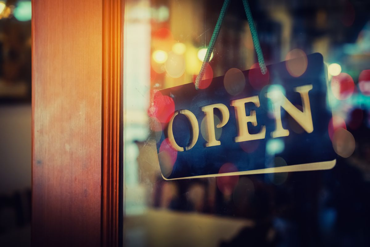 """A sign outside a restaurant window with wood framing says """"Open"""""""